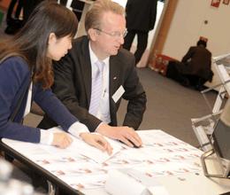 Arbeitgeber erläutert dem Bewerber am Stand die Anforderungen eines Stellenangebotes während der Jobmesse